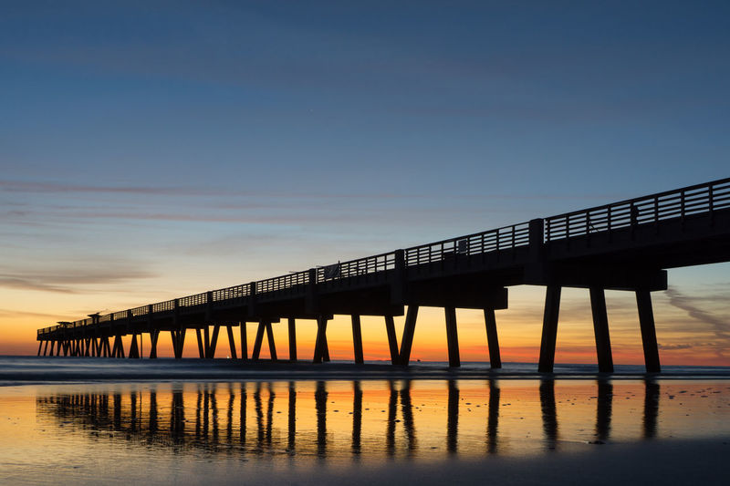 Low angle view of silhouette pier at sea against sky during sunset