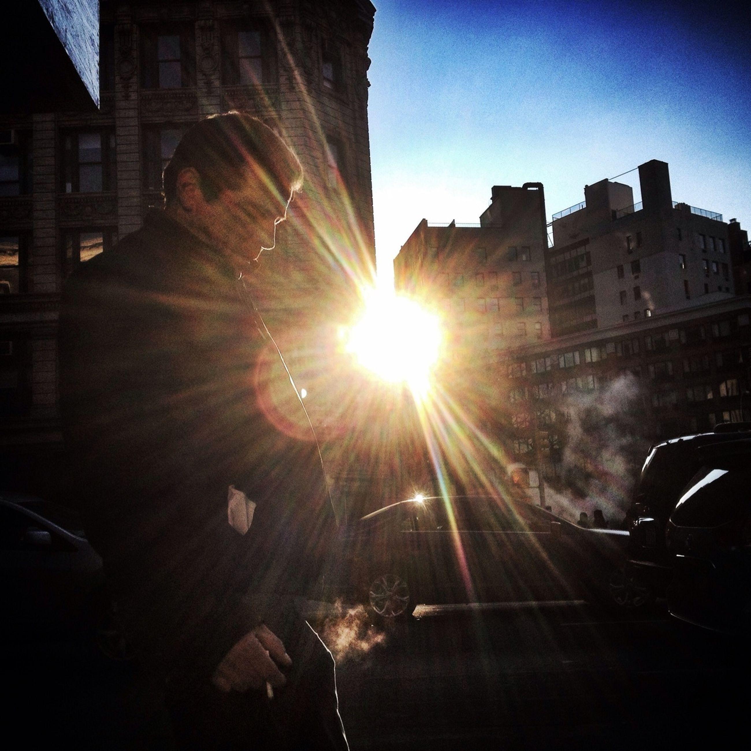 transportation, building exterior, architecture, built structure, land vehicle, mode of transport, car, city, sun, street, sunbeam, sunlight, lens flare, road, building, city street, sky, city life, travel, on the move