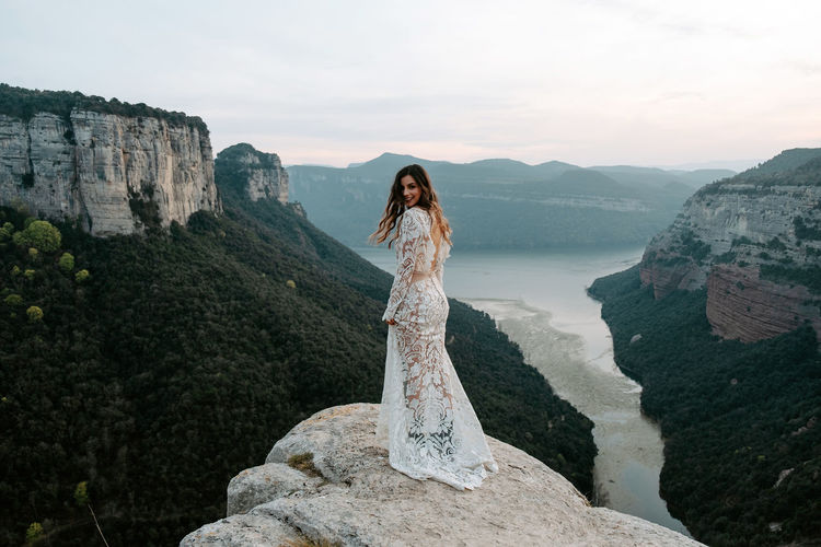 Woman standing on rock by mountain against sky