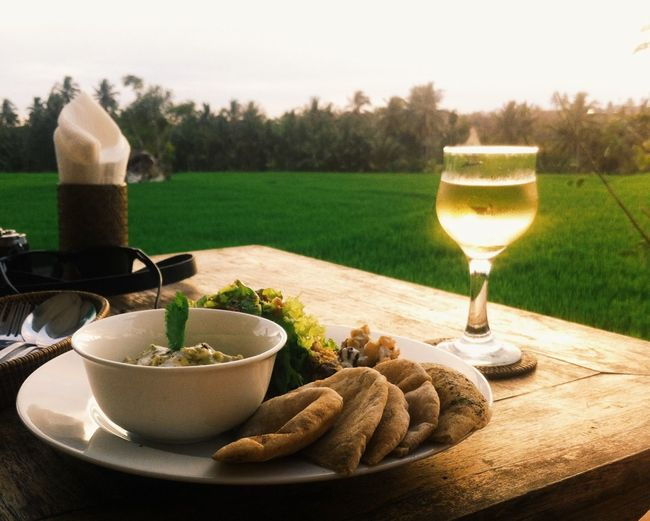 High angle view of food with white wine on table at lawn