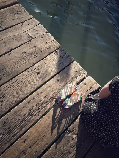 Midsection of woman sitting on wooden pier by lake