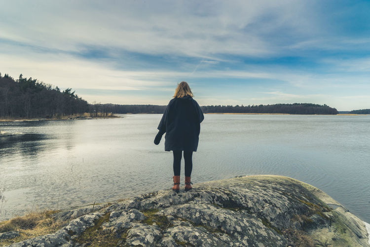 Rear View Of Woman Standing On Rock In Lake Against Sky