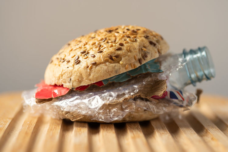 Fresh tasty burger with plastic waste and paper cardboard inside on wooden board. Recycled waste in our food concept Bread Breakfast Close-up Cutting Board Food Food And Drink Freshness Healthy Eating Indoors  Indulgence No People Plastic Ready-to-eat Recycling Sandwich Selective Focus Snack Still Life Studio Shot Table Temptation Vegetable Waste Wellbeing Wood - Material Plastic Environment - LIMEX IMAGINE