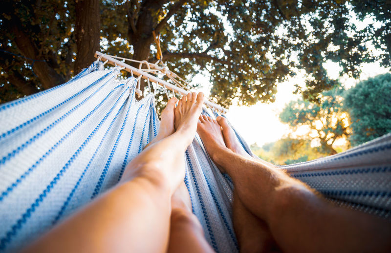 Midsection of woman relaxing on hammock