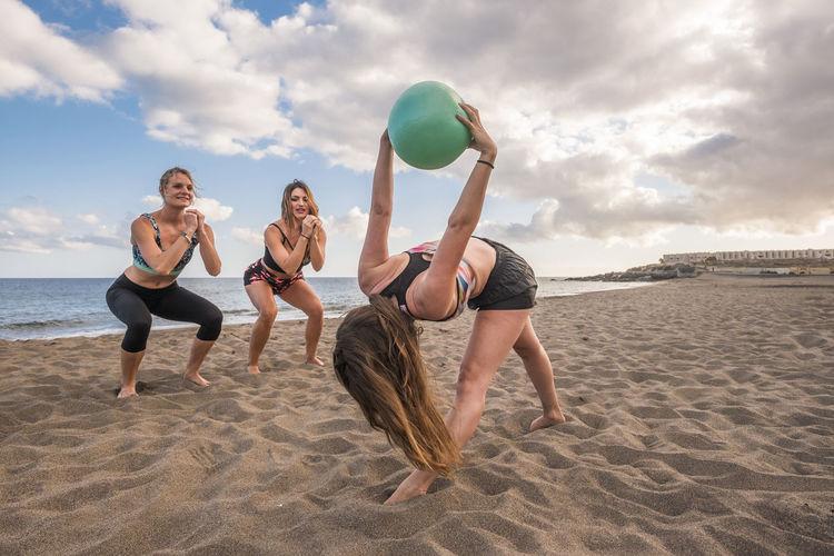 Full length of friends exercising on sand at beach against sky
