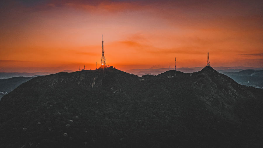 Silhouette tower on landscape against sky during sunset