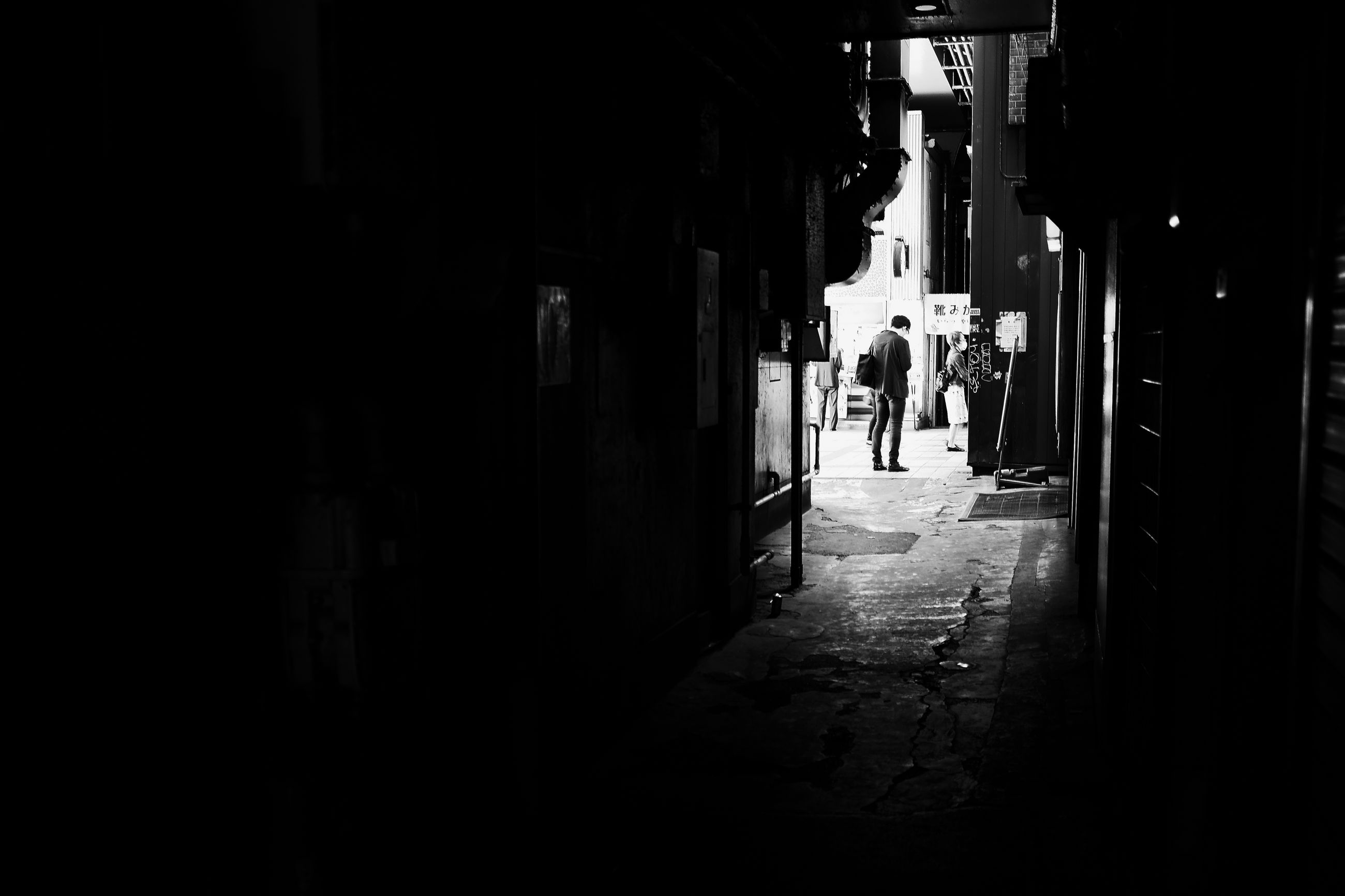 architecture, built structure, real people, walking, group of people, city, lifestyles, men, the way forward, direction, people, building, day, dark, building exterior, outdoors, women, leisure activity, footpath, silhouette, alley