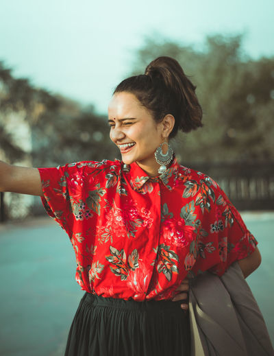 Smiling young woman standing outdoors
