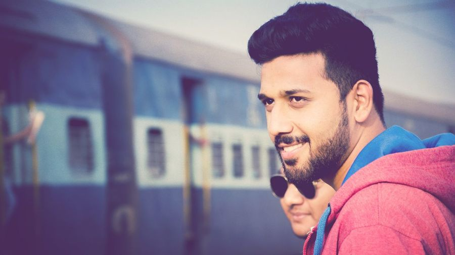 Close-up of smiling young man with friend against train at railroad station