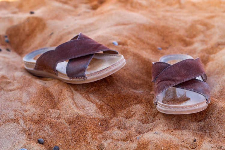 Close-up of shoes on the sand