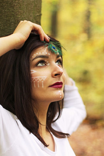 Close-up of young woman with painted face holding peacock feather