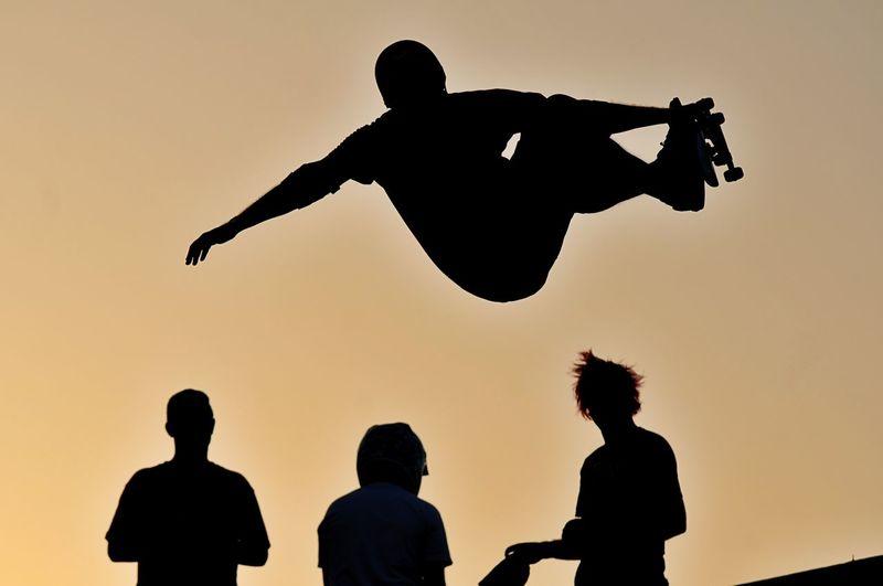 Silhouette man skateboarding against clear sky