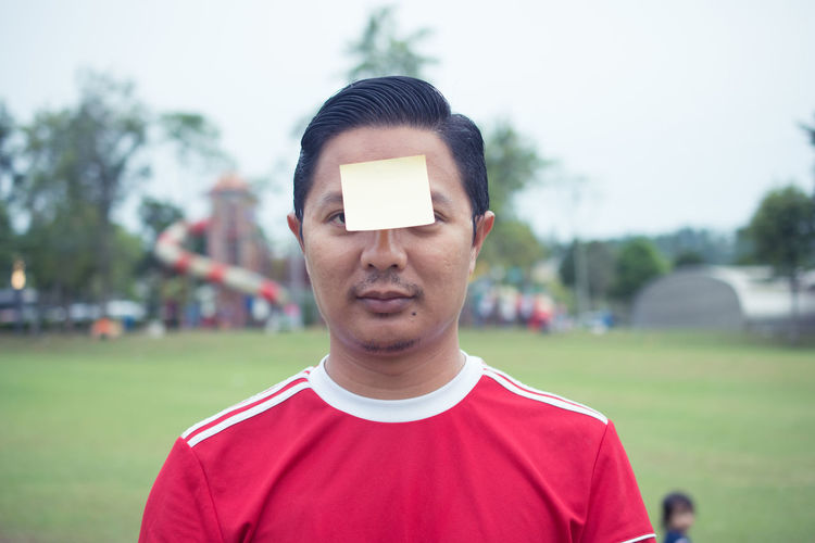 Portrait Of Mid Adult Man With Adhesive Note On Forehead On Soccer Field