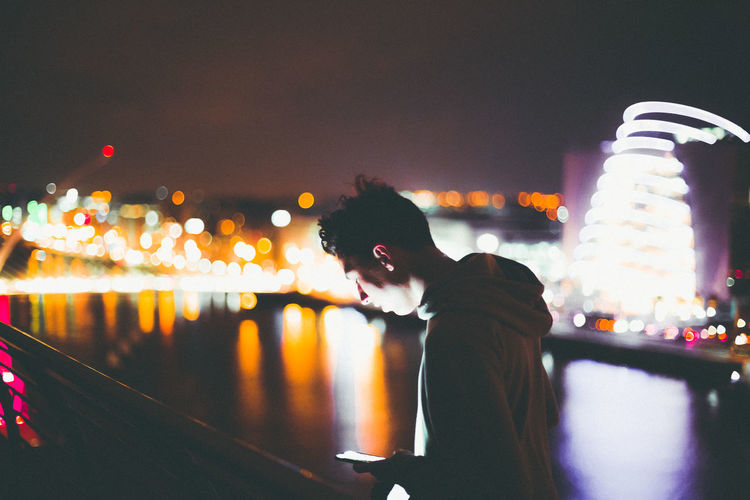 Young man using mobile phone while standing against illuminated buildings by river at night