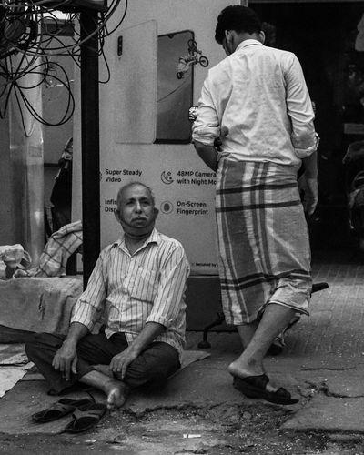 Rear view of friends sitting on street