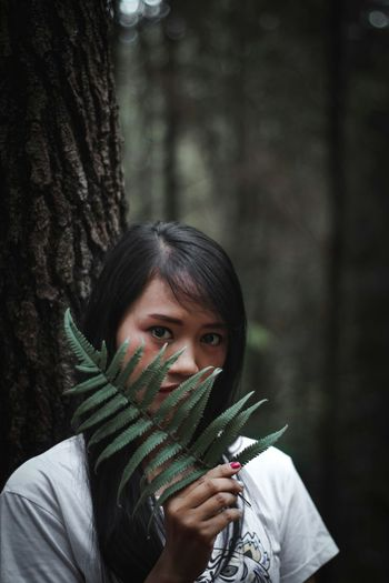 Portrait of happy girl holding tree trunk in forest