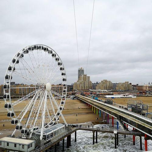 Ferris wheel by river against sky in city