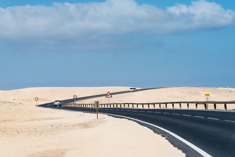 Scenic road through sand dunes against sky Canary Islands Desert Dunes Fuerteventura Transportation Architecture Beach Bridge Bridge - Man Made Structure Built Structure Cloud - Sky Connection Corralejo Day Land Nature No People Outdoors Road Sand Sea Sky Sunlight Transportation Water Wild Road