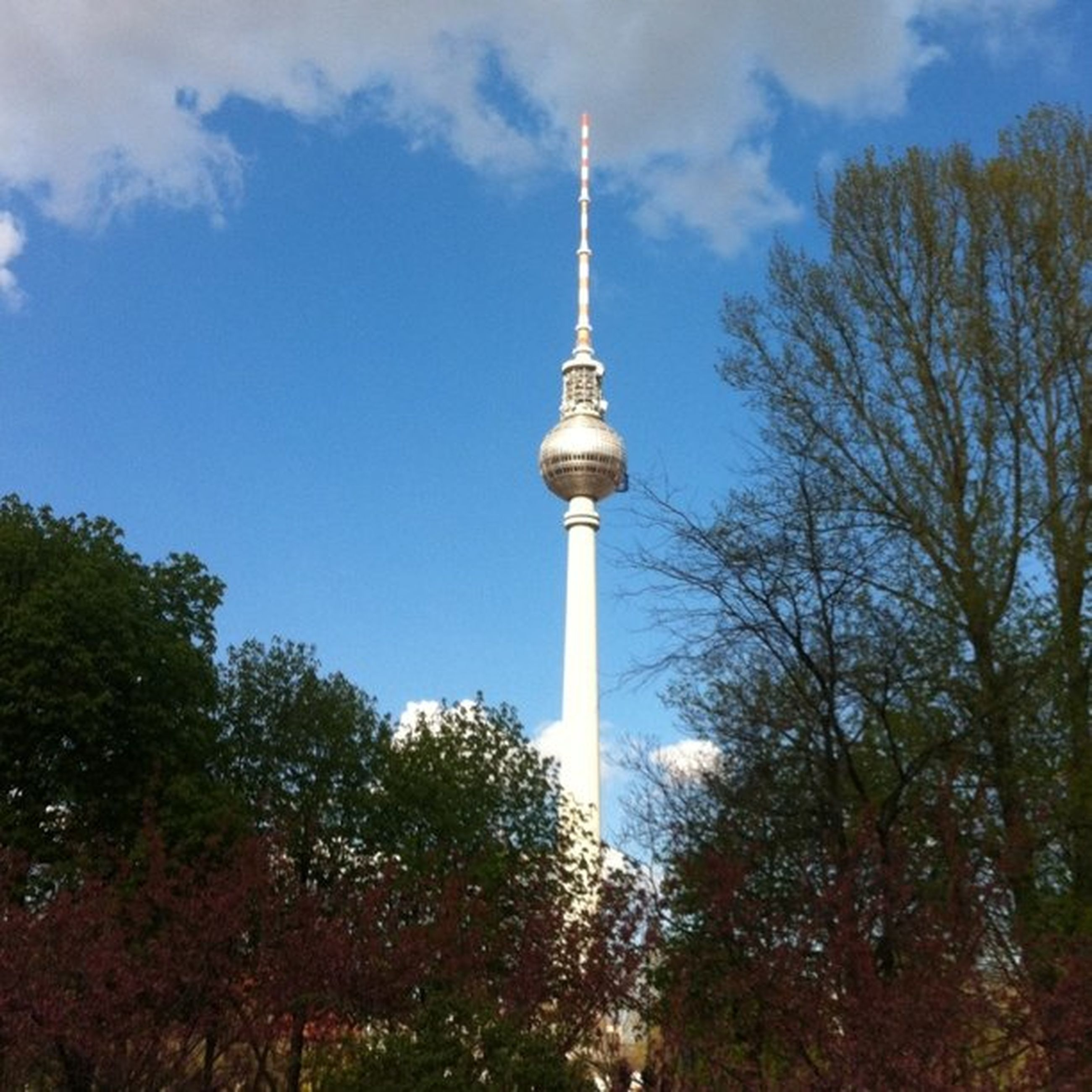 communications tower, tower, tall - high, architecture, built structure, low angle view, fernsehturm, building exterior, television tower, spire, communication, sky, tree, travel destinations, culture, famous place, tourism, sphere, capital cities, international landmark