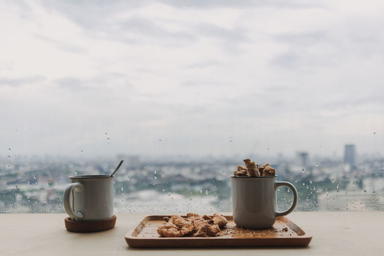 Coffee cup on table against sky
