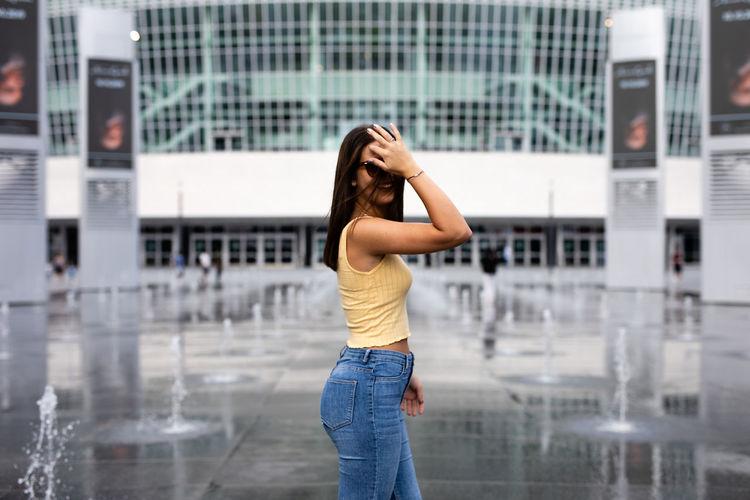 Side view of woman standing in city