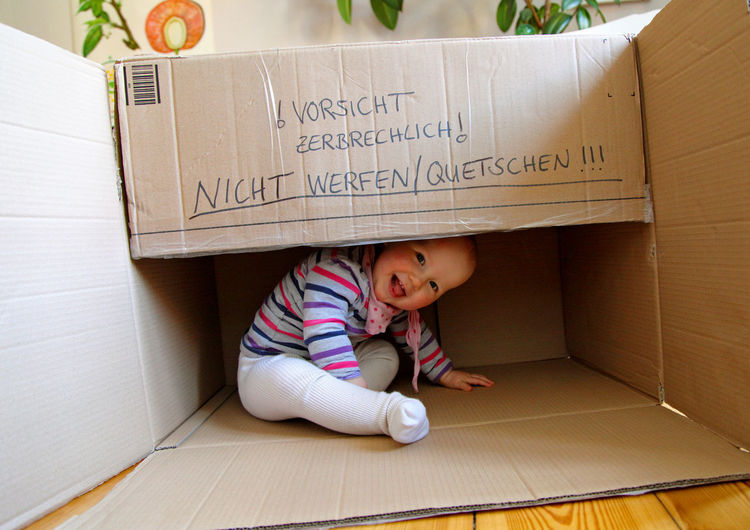 High angle view of cute girl sitting on floor at box
