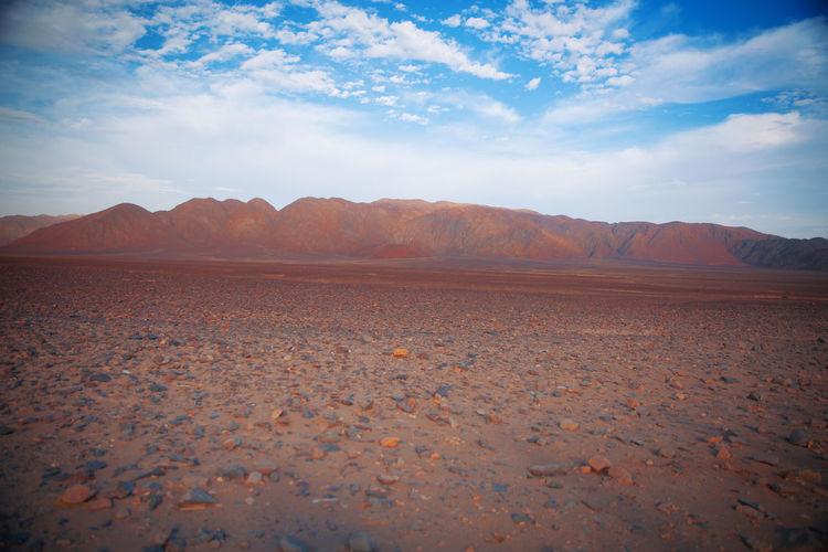 Surface level of barren land against sky