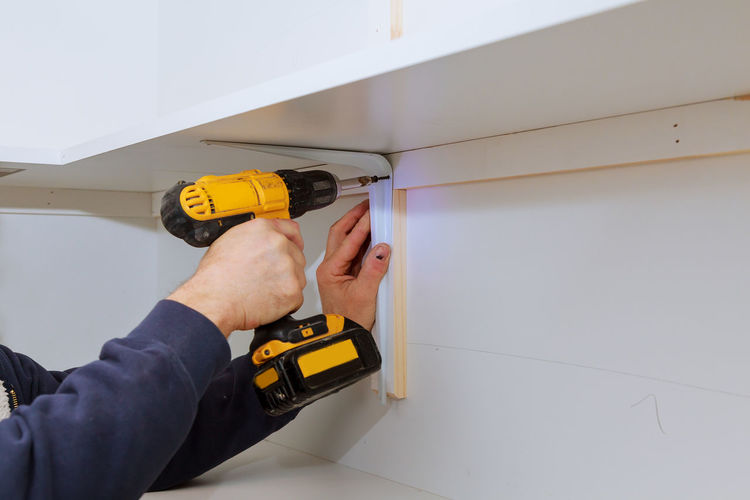 Cropped Hand Of Man Working With Nail Gun At Home