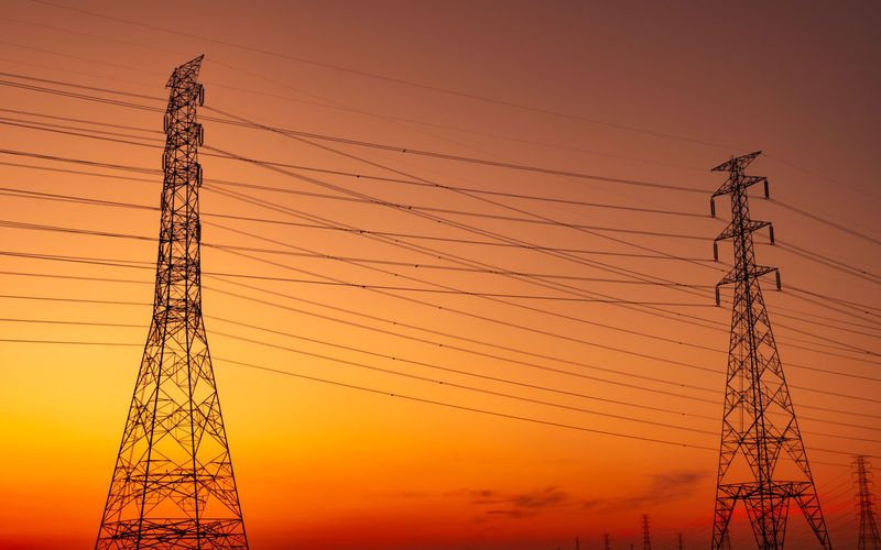 Low angle view of silhouette electricity pylon against romantic sky