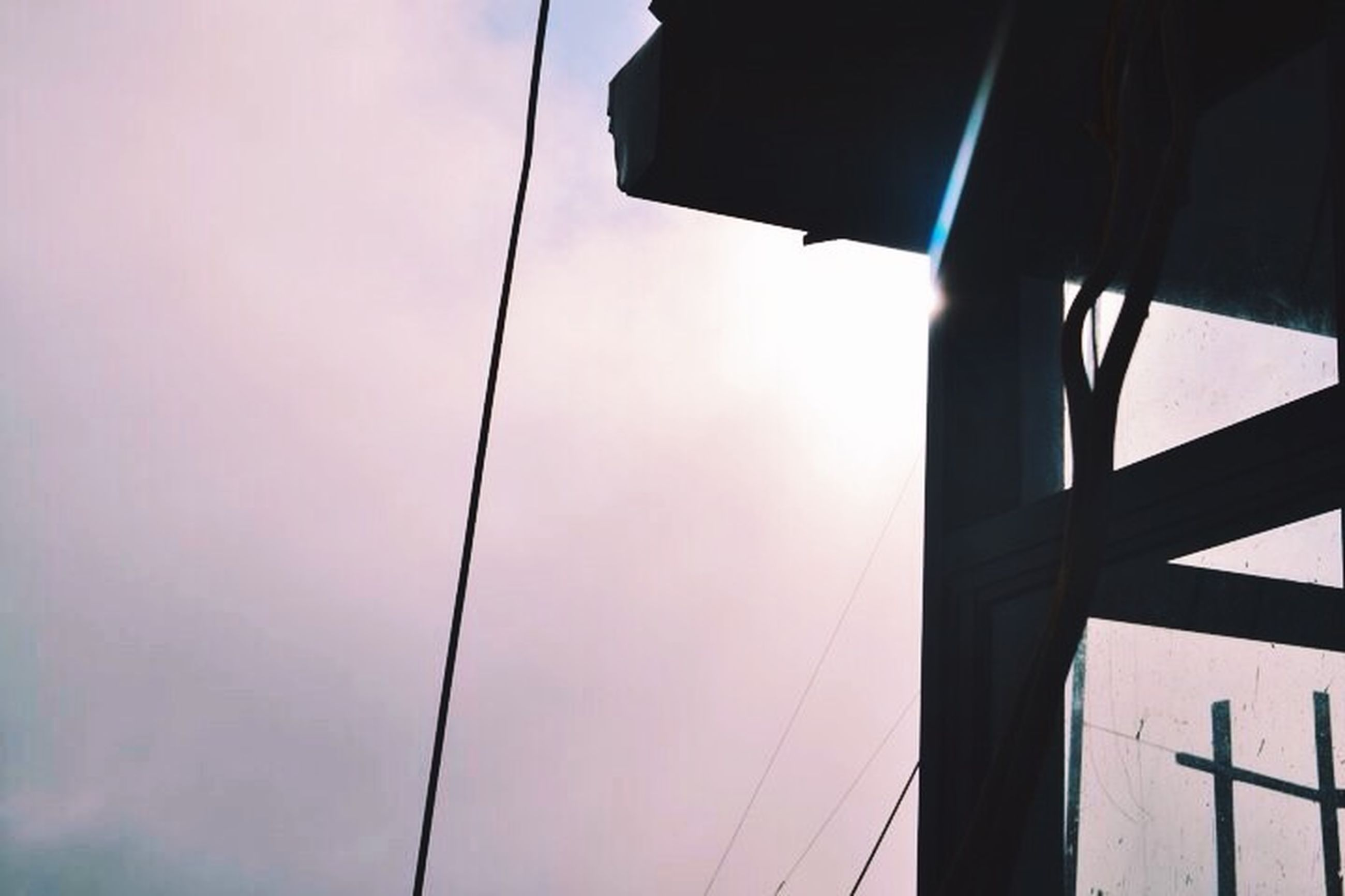 low angle view, sky, built structure, architecture, power line, cable, silhouette, electricity, connection, building exterior, sunlight, part of, clear sky, no people, street light, outdoors, electricity pylon, day, pole, power supply