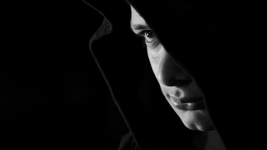 Close-Up Of Man In Hood Clothing Against Black Background