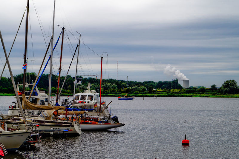 Boats Moored On River Against Silo Emitting Smoke In Sky