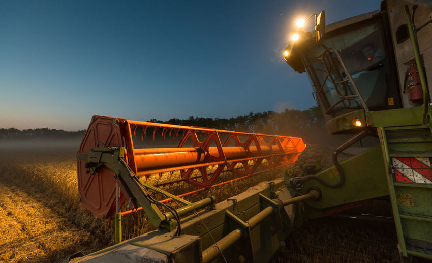 Illuminated machine harvesting crops on field at dusk