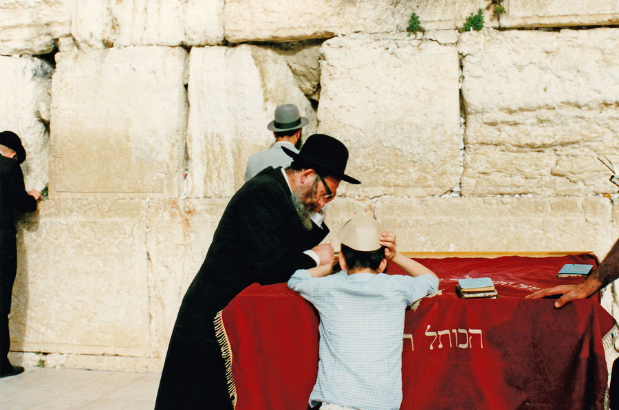 "A Rabbi with a young boy at the Western Wall - Jerusalem, Israel The Western Wall, or ""Wailing Wall"", is the most religious site in the world for the Jewish people. Located in the Old City of Jerusalem, it is the western support wall of the Temple Mount. Thousands of people journey to the wall every year to visit and recite prayers. These prayers are either spoken or written down and placed in the cracks of the wall. The wall is divided into two sections, one area for males and the other for females. It is one of the major highlights in any tour of the Old City. Architecture People Real People Men Women Day Standing Outdoors Bonding Togetherness Adult Lifestyles Young Adult Rabbi Two People Wailing Wall Temple Mount Orthodox Jews Building Exterior Built Structure Red Cloth Western Wall Of Jerusalem Hebrew Text Jewish Rabbi Jewish Peoples An Eye For Travel Stories From The City Inner Power This Is Aging My Best Travel Photo A New Beginning Autumn Mood"