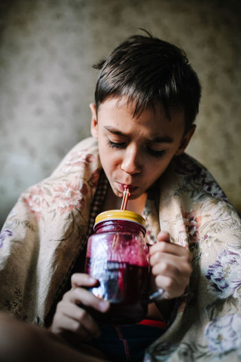Boy drinking juice in container