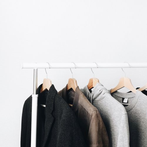 Sweaters hanging on rack against wall