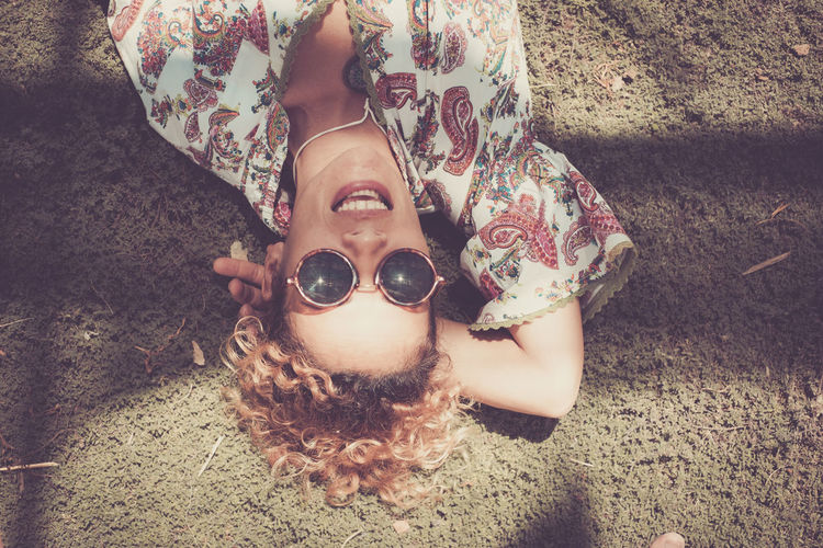 High angle portrait of smiling young woman lying on field