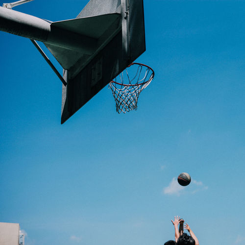 Low angle view of people playing basketball against blue sky