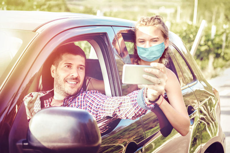 Young couples on road trip taking selfie with face mask while driving on countryside