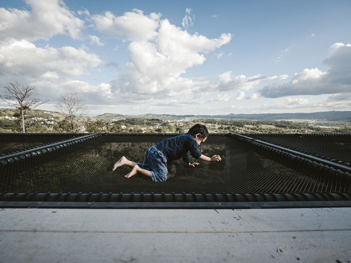 Side view of boy crawling on netting against sky