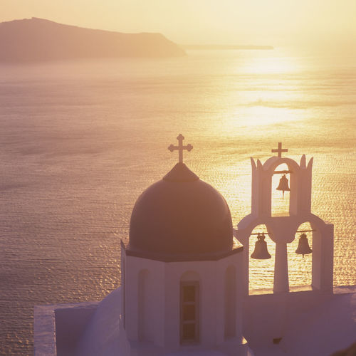 Cross on sea shore against sky during sunset