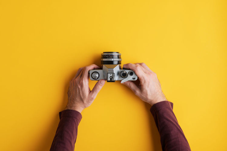 Close-up of hand holding camera against yellow background