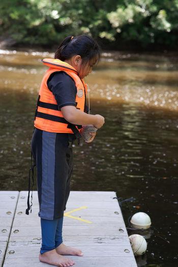 Full length of cite girl feeding fish in lake