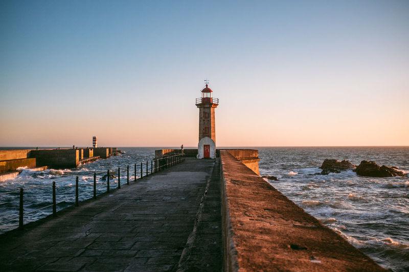Lighthouse on pier against clear sky