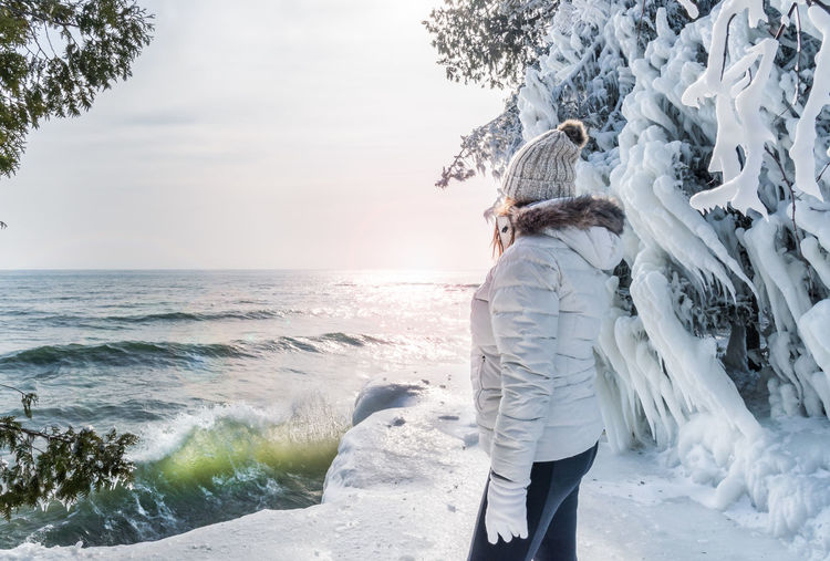 Woman standing by sea against sky during winter