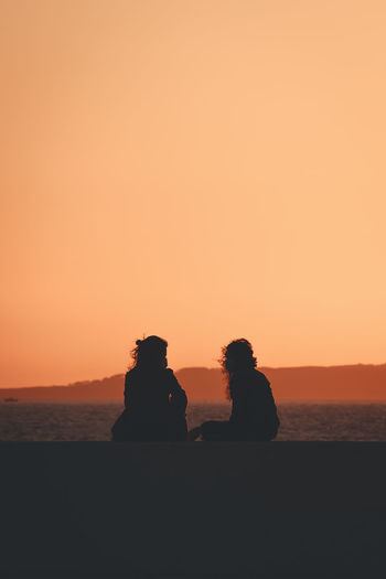 Silhouette people sitting against orange sky during sunset