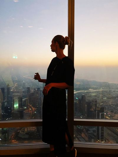 Young woman looking at cityscape through window