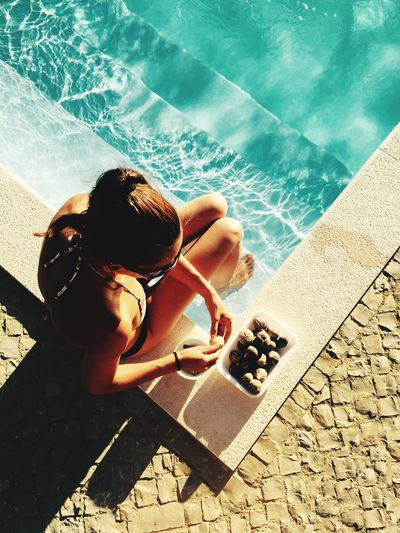High angle view of young woman eating fruits while sitting at poolside