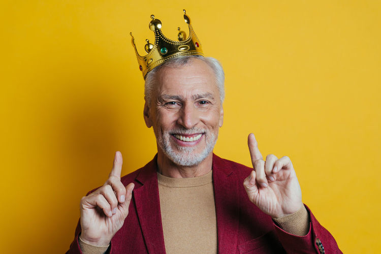 Portrait of smiling man gesturing against yellow background
