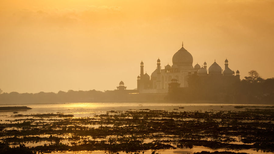 Beautiful long exposure nature sunrise scenery with Taj Mahal silhouette and colouful sky during travel at Agra, INDIA Agra India Architecture Building Exterior Built Structure City Cityscape Cultures Day Dome Government History India No People Outdoors Place Of Worship Politics And Government Reflection Shah Jehan Silhouette Sky Sunrise Sunset Taj Mahal Travel Destinations Water